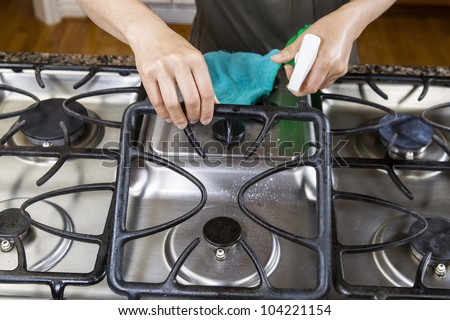 Hands lifting front grill of stove top range with spray bottle in hand - stock photo