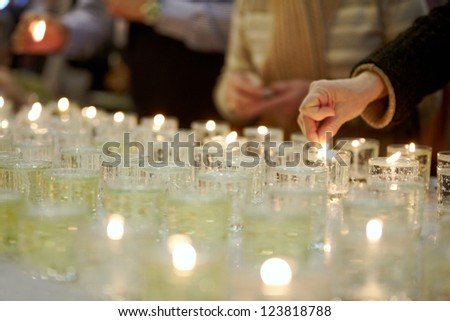 Hands lighting funeral candles - stock photo