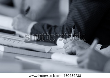 Hands make notes on a seminar - stock photo
