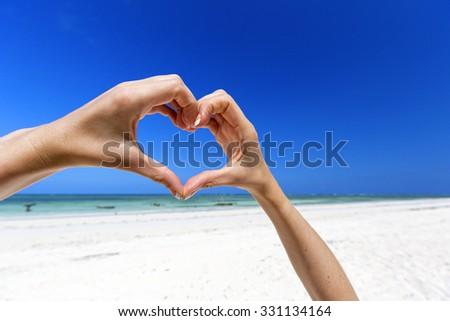 Hands making a heart shape against a blue sky. Tropical paradise. - stock photo