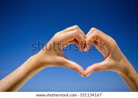 Hands making a heart shape against a blue sky. Tropical paradise.