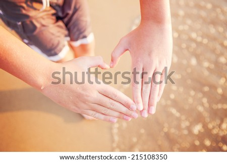 Hands making a heart shape at the beach  - stock photo