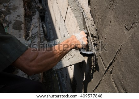 hands making cement wall