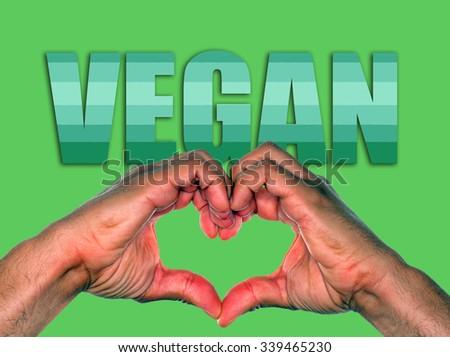 Hands making heart over green background, for vegan or veganism environmental concept - stock photo
