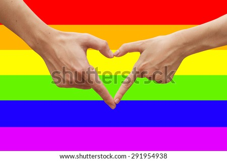 hands making heart shape on rainbow flag backgrounds, gay love concept - stock photo