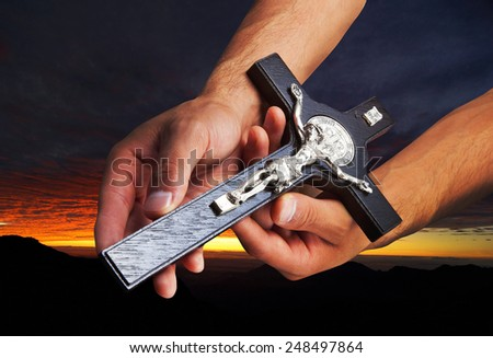 Hands man with crucifix in sunset background - stock photo