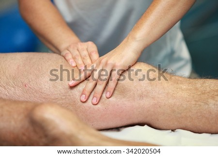 hands massaging athlete's thigh after running - stock photo