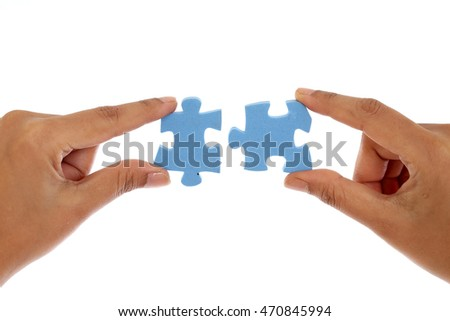 Hands merging two jigsaw puzzle pieces against white background