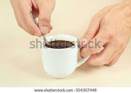 Hands mixing with a spoon of hot coffee in the cup - stock photo