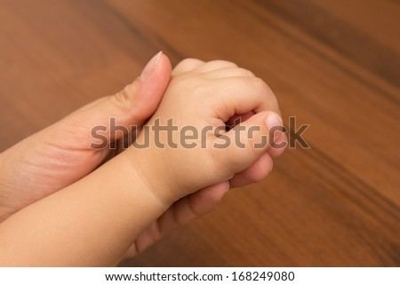 Hands mother and son - stock photo