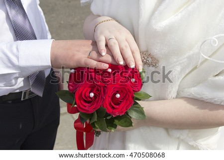 Hands newlyweds on a red bouquet. CONCEPT wedding