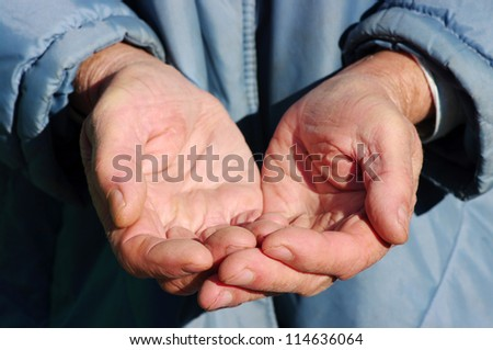 hands of a beggar with coins - stock photo