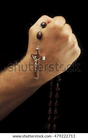 Hands of a believer with a wooden rosary