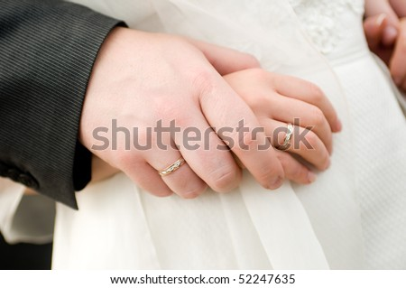 hands of a bride and a groom with wedding rings