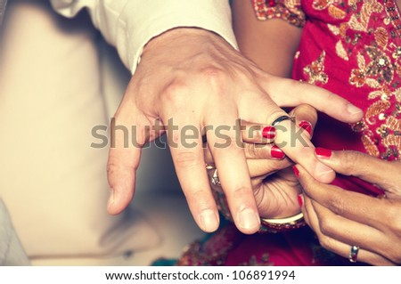 Hands of a bride and groom wearing rings. vintage color
