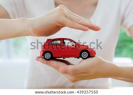 hands of a business woman holding a red toy car isolated - stock photo