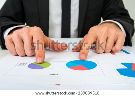 Hands of a businessman analysing two pie graphs as he sits at his desk pointing to one pie graph, in a business strategy concept. - stock photo