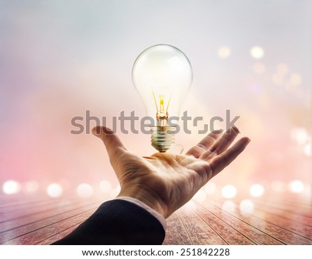 Hands of a businessman reaching to towards light bulb on wooden pastel background  - stock photo