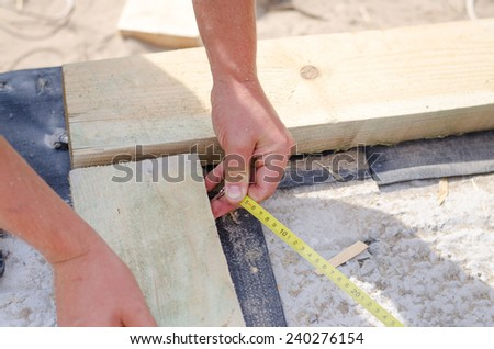 Hands of a carpenter taking a diagonal measurement on a new build building site as he aligns to wooden corner beams - stock photo