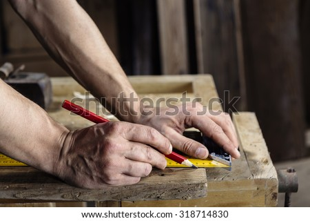 hands of a carpenter taking measurement of a wooden plank with pencil and ruler - stock photo
