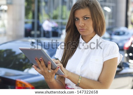 Hands of a casual woman holding a digital tablet.