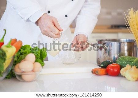 Hands of a chef pouring milk into a bowl.