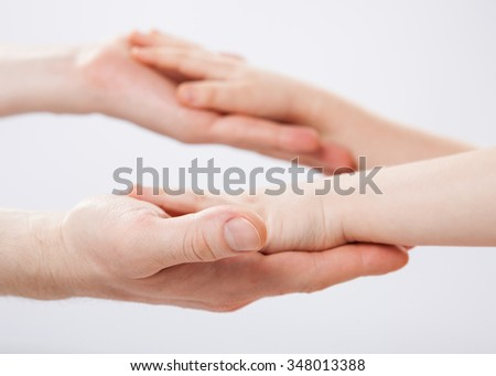 Hands of a child and a father holding each other, closeup shot