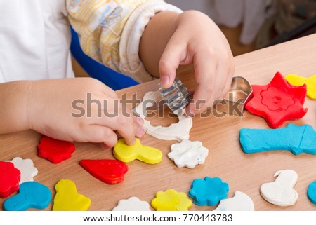 Hands of a Child make figurines of modeling clay