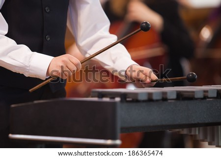 Hands of a child playing a xylophone - stock photo