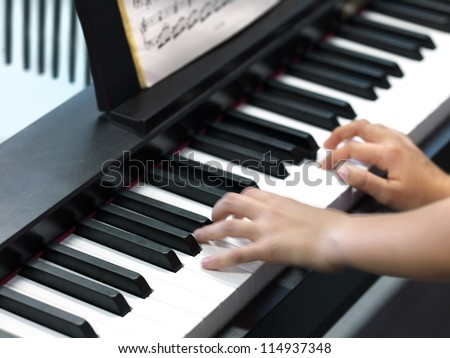 hands of a child playing the piano - stock photo