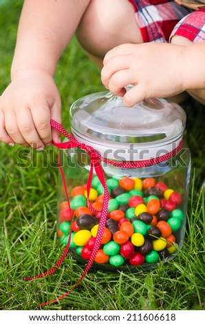 Hands of a child trying to open a jar of candies - stock photo