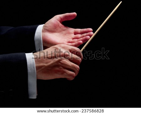 Hands of a conductor on black background - stock photo