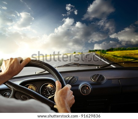 Hands of a driver on steering wheel of a car and empty asphalt road - stock photo