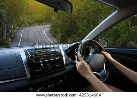 Hands of a driver on steering wheel of a car on road