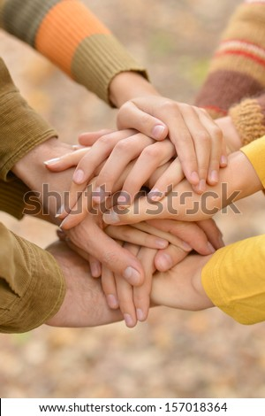Hands of a family together closeup on autumn background - stock photo