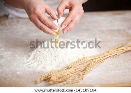 Hands of a female bakery chef breaking an egg into a heap of measured flour while making bread with a bunch of wheat alongside - stock photo