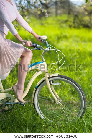 Hands of a female holding handbrake on vintage bicycle and graceful leg at the pedal on the blurred background of fresh greenery