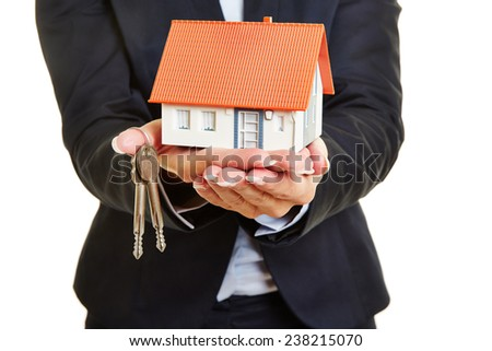 Hands of a female real estate broker holding a small house and keys - stock photo