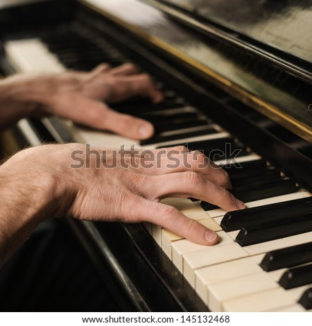 Hands of a genius. Close-up shoot of hands touching piano keys - stock photo