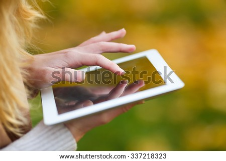 Hands of a girl holding tablet computer in autumn forest