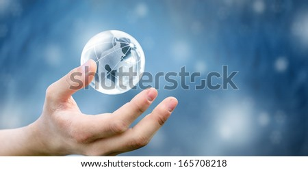 Hands of a glass planet in New Year - stock photo