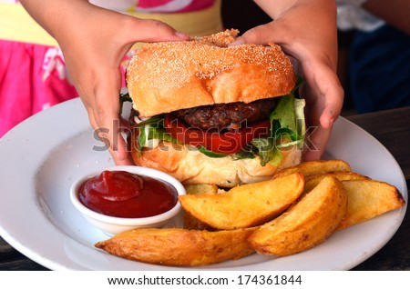 Hands of a little girl  ready to eat a big hamburger. concept photo - stock photo