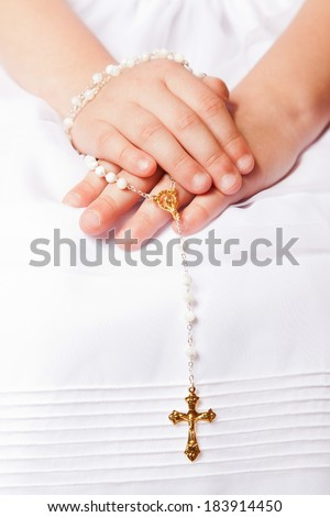 Hands of a little her in the First Communion Day Holding a Golden Cross - stock photo