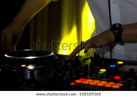 Hands of a male disc jockey mixing music on his deck and turntables at night with colourful lighting on the switches and controls - stock photo