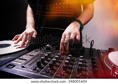Hands of a male DJ scratching hip hop music record and playing on professional sound mixer - stock photo