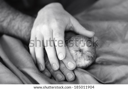 Hands of a man and woman in bed with apple. Concept photo for sex health care, sex life, seduction, sexual, sexuality, relationship, sex problems, desire, lust, love. - stock photo