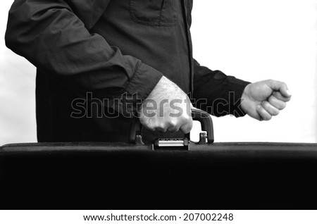 Hands of a man carry travel suitcase against white background with copy space. Concept photo of travel, vacation, holiday, destination, tourism, traveler, tourist.(BW) - stock photo