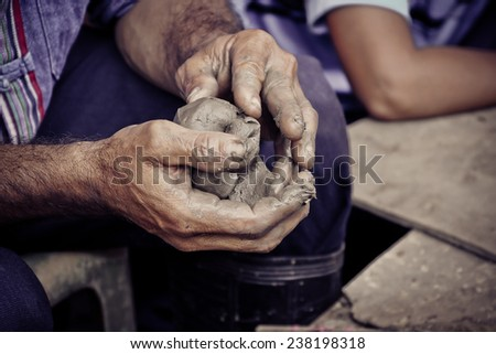 hands of a man, creating an earthen jar on the circle - stock photo