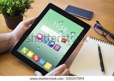 hands of a man holding a tablet device over a wooden workspace table. All screen graphics are made up. - stock photo