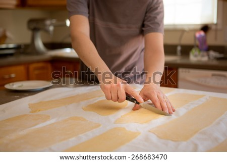 Hands of a man preparing fresh homemade fettuccine pasta trimming the sheets of rolled dough into rectangles to feed through the cutter on a table in a domestic kitchen - stock photo